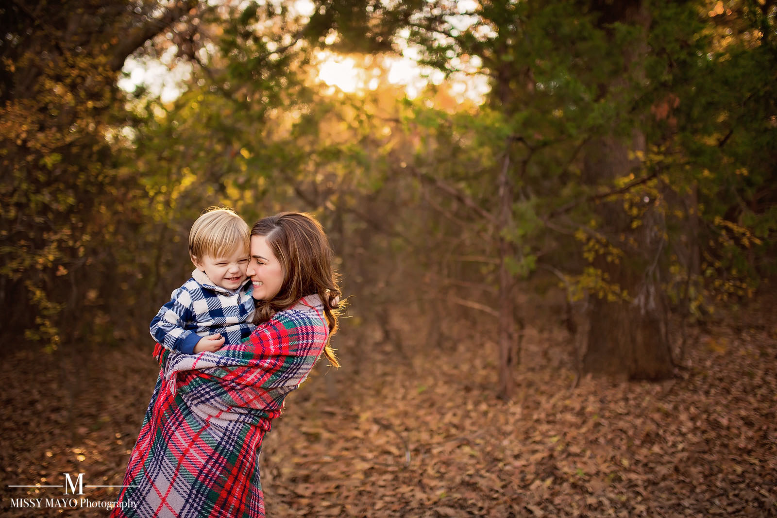 mom cuddling baby in a plaid blanket outdoors by Missy Mayo