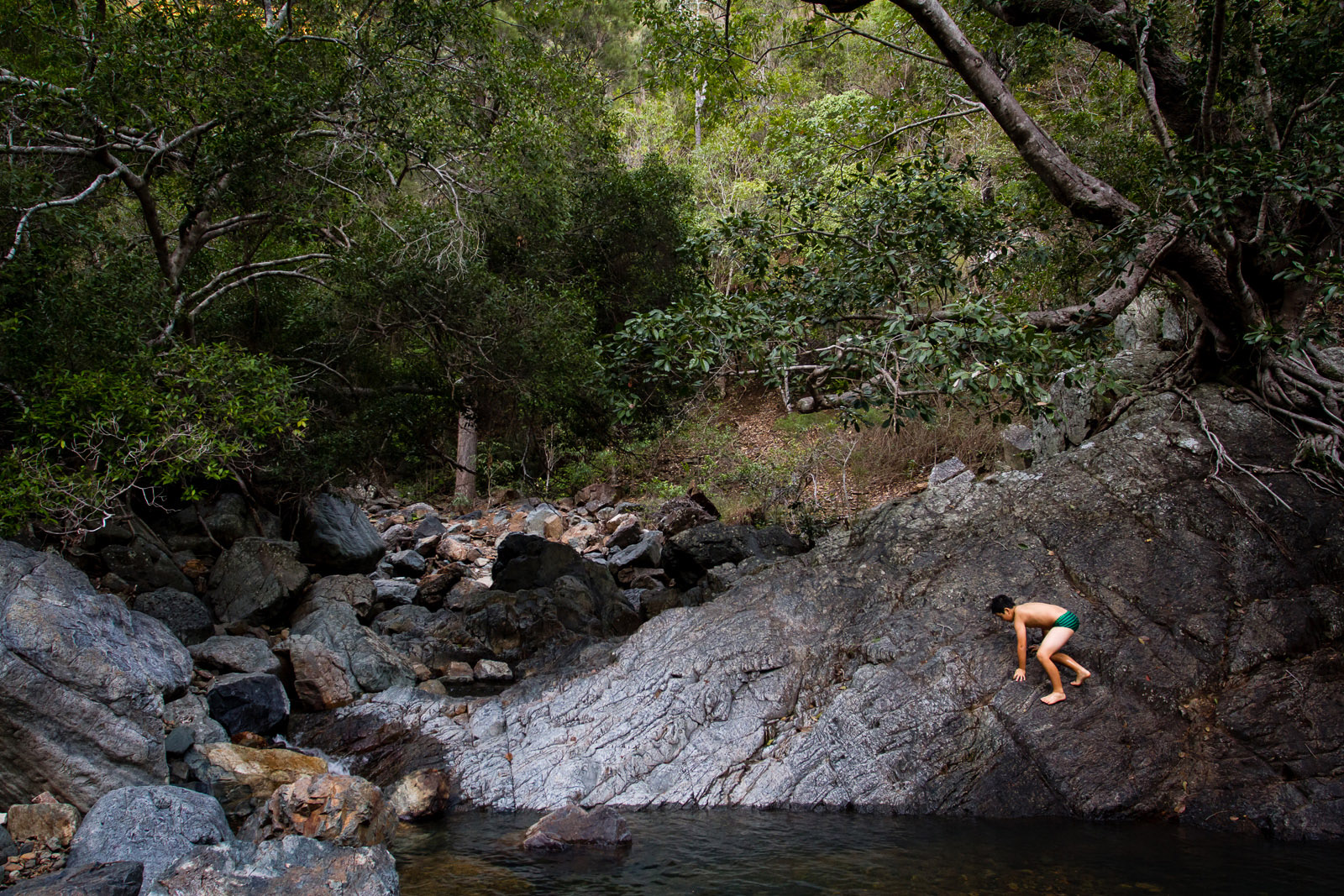 photo of boy climbing rocks by the water by Jayne Cho