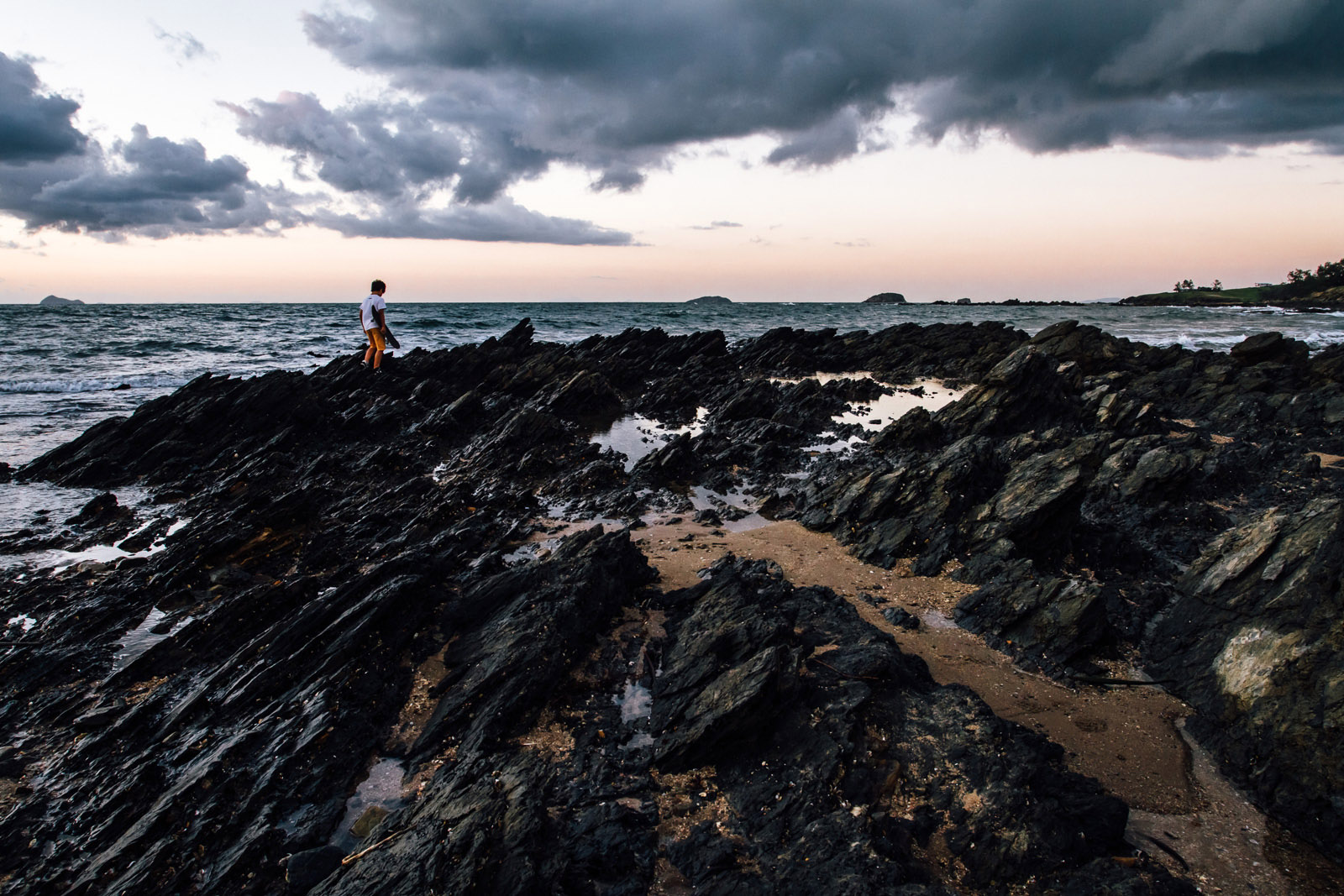 photo of boy walking on rocks by the water by Jayne Cho