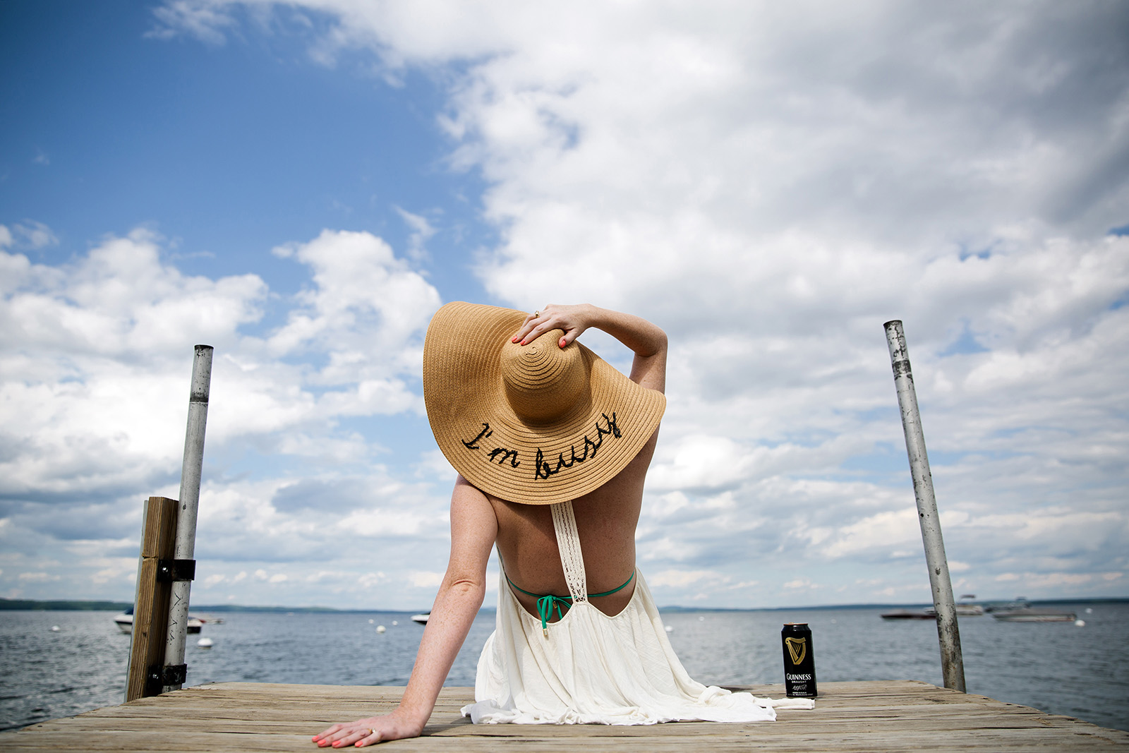 pic of woman with an I'm Busy hat on a pier by Olivia Gatti