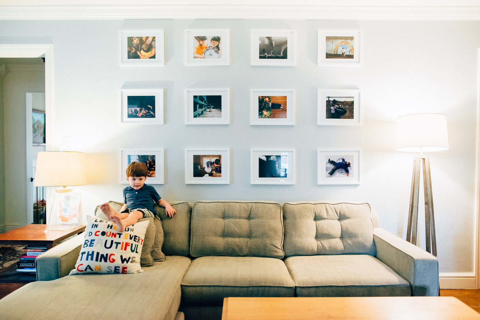 picture of a boy sitting on a couch with photos on the wall by Andrea Moffatt