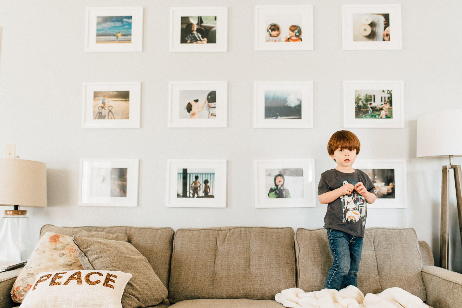 picture of kid standing on a couch with photos on the wall behind him by Andrea Moffatt