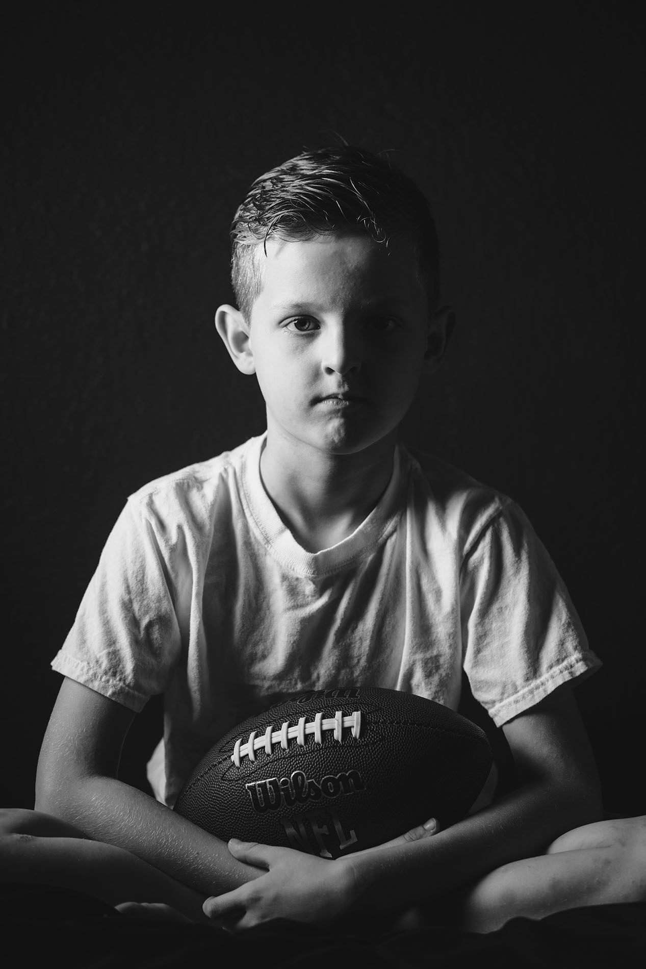 split light black and white photo of boy holding a football by April Nienhuis