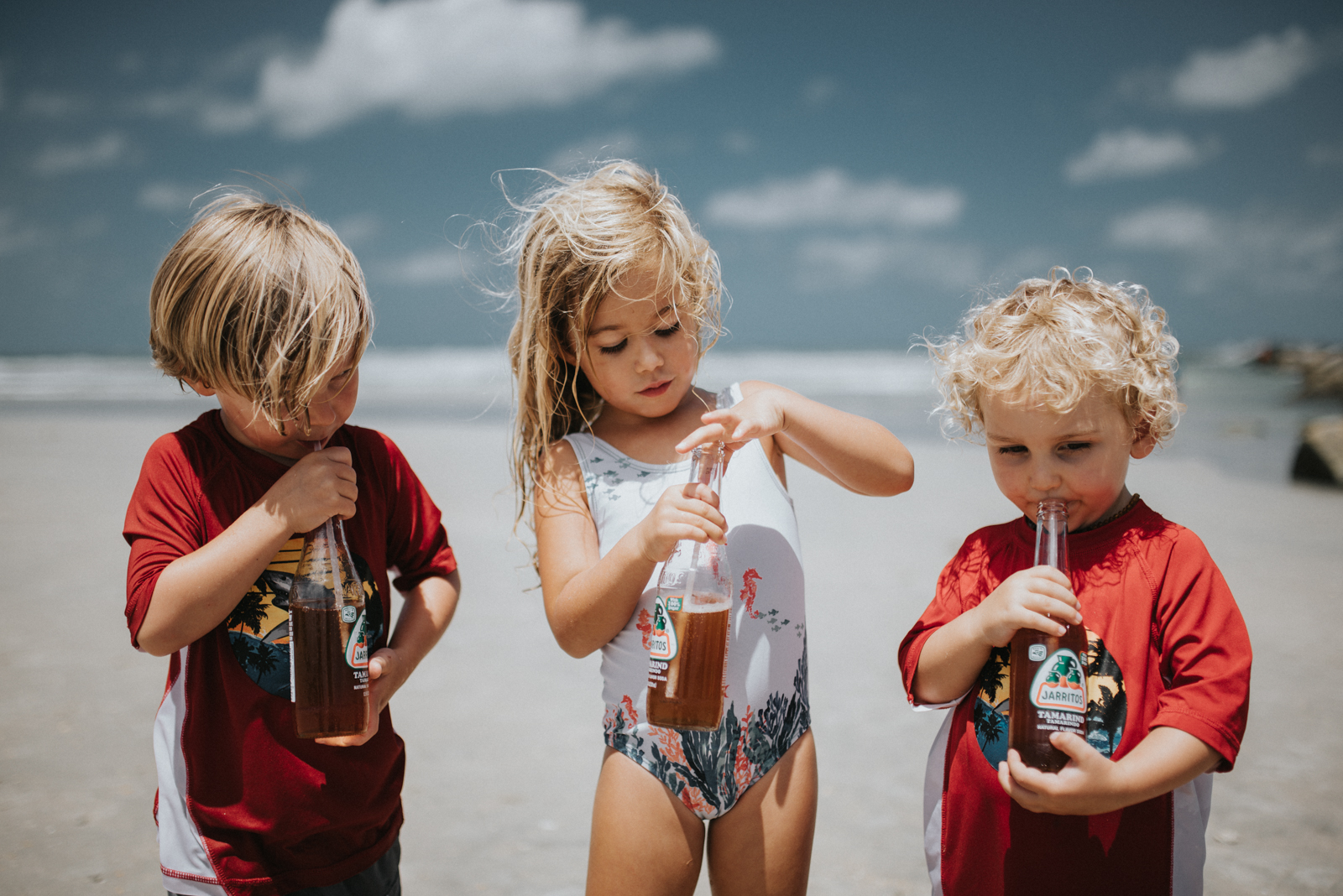 three kids drinking pop on the beach by Twyla Jones