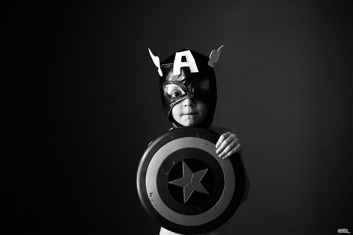 black and white picture of boy dressed like Captain America by Heather Stockett