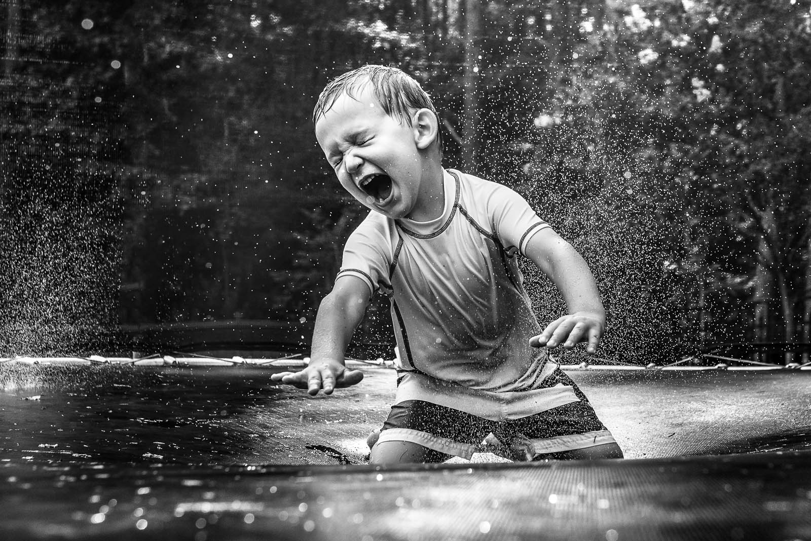 black and white picture of kid getting wet on a trampoline by Susan Grimes