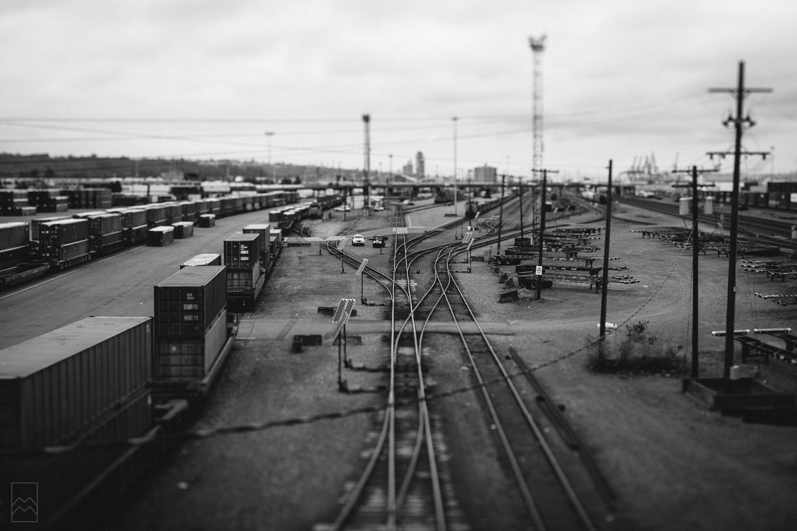 black and white tilt-shift photo of train tracks to look miniature by Meghan McMackin