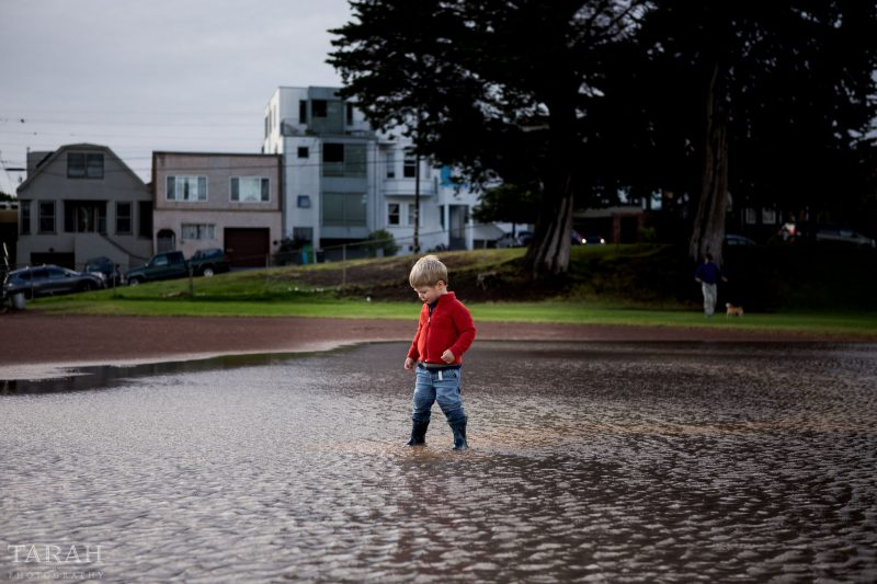 photo of boy playing in a large water puddle in the city by Tarah Beaven