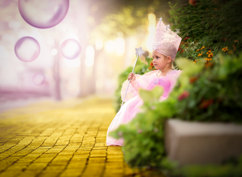 photo of little girl dressed as Glenda the good witch near a yellow brick road by Kate Luber