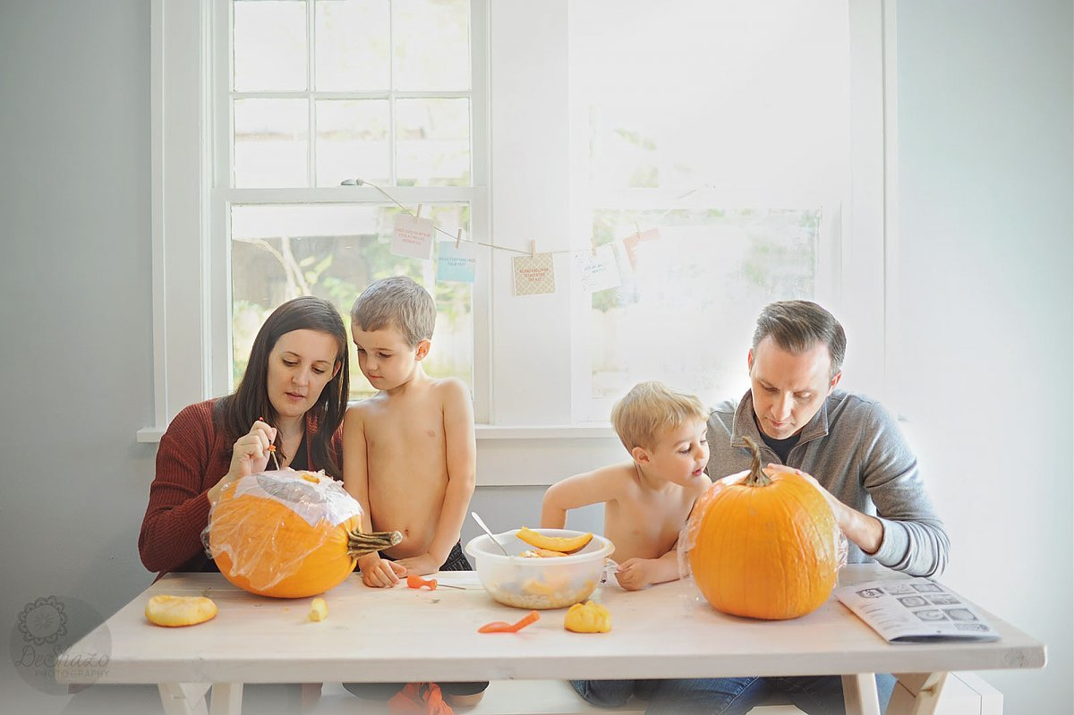 pic of family carving pumpkins together by Megan DeShazo