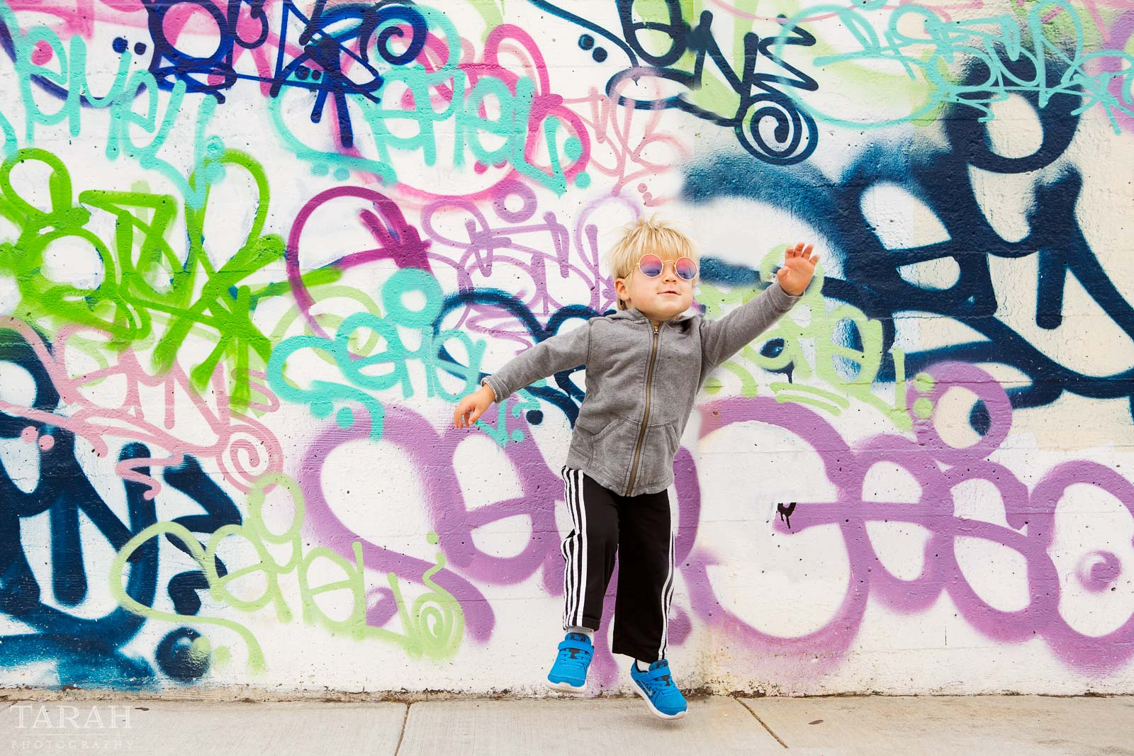 pic of kid by a grafitti wall by Tarah Beaven