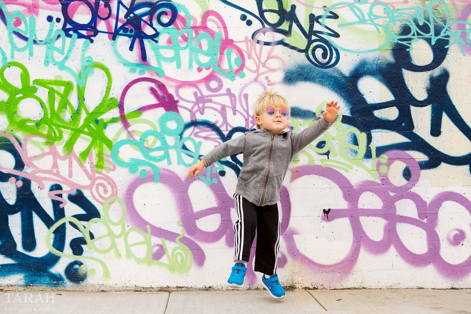 pic of kid by a grafitti wall by Tarah Beaven big city