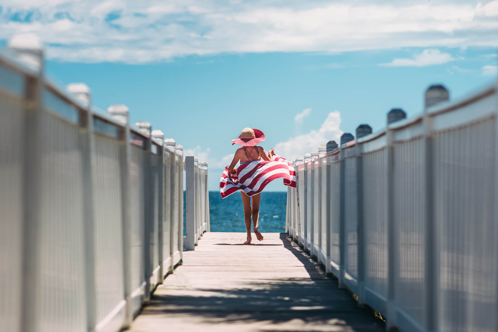 picture of girl walking on the beach with a striped towel by Susan Grimes