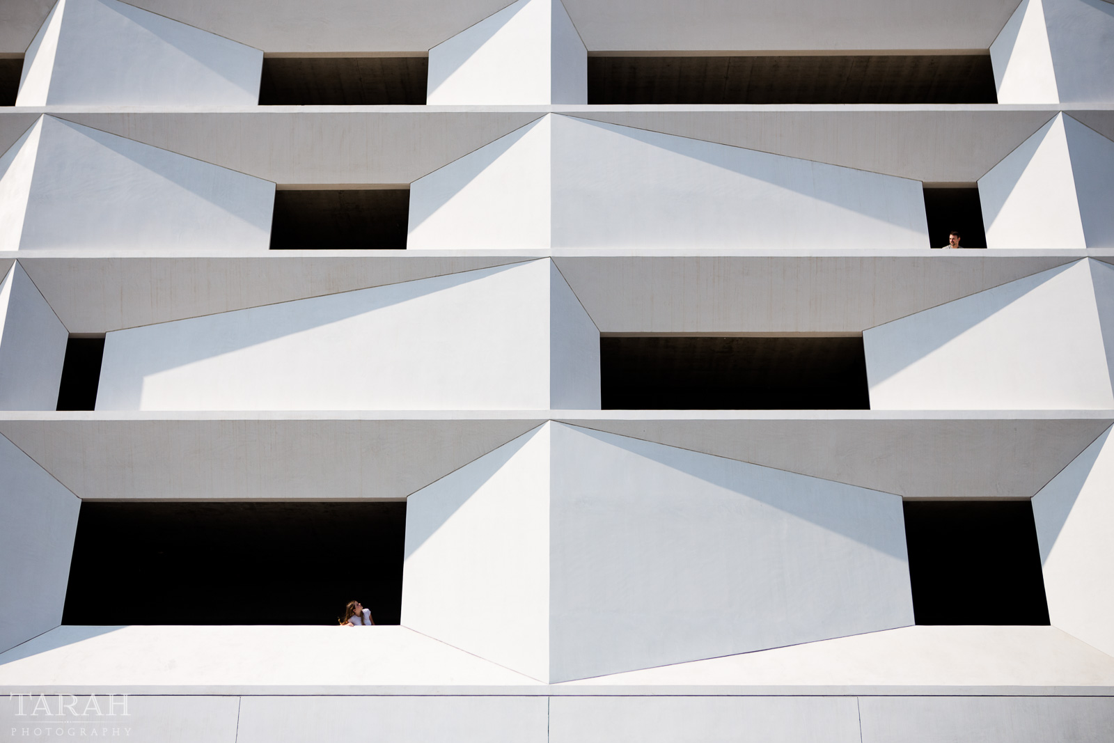 picture of people looking out windows of a parking garage by Tarah Beaven