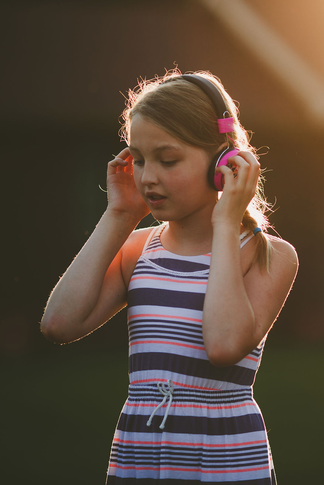 rim light picture of girl listening to her headphones by April Nienhuis
