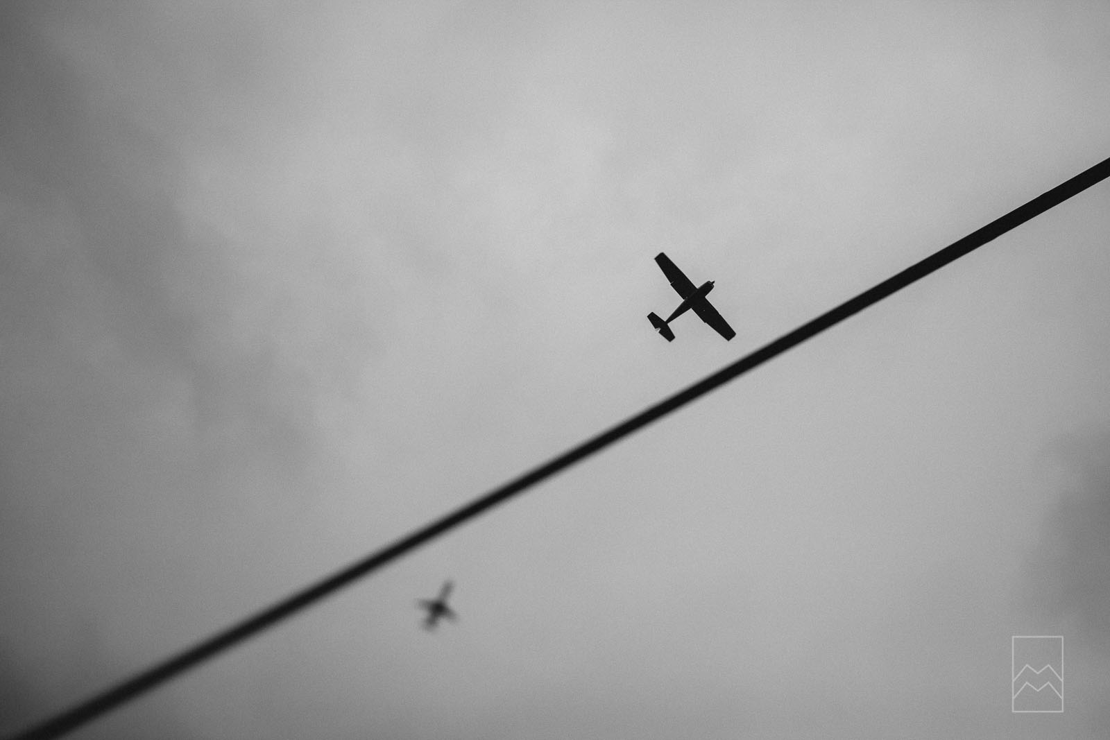 tilt-shift picture of airplanes flying in the sky by Meghan McMackin