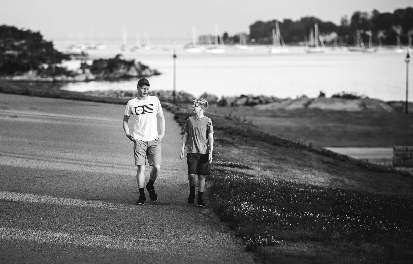 Black And White Photo Of Brothers Walking Talking By Amy Nowak