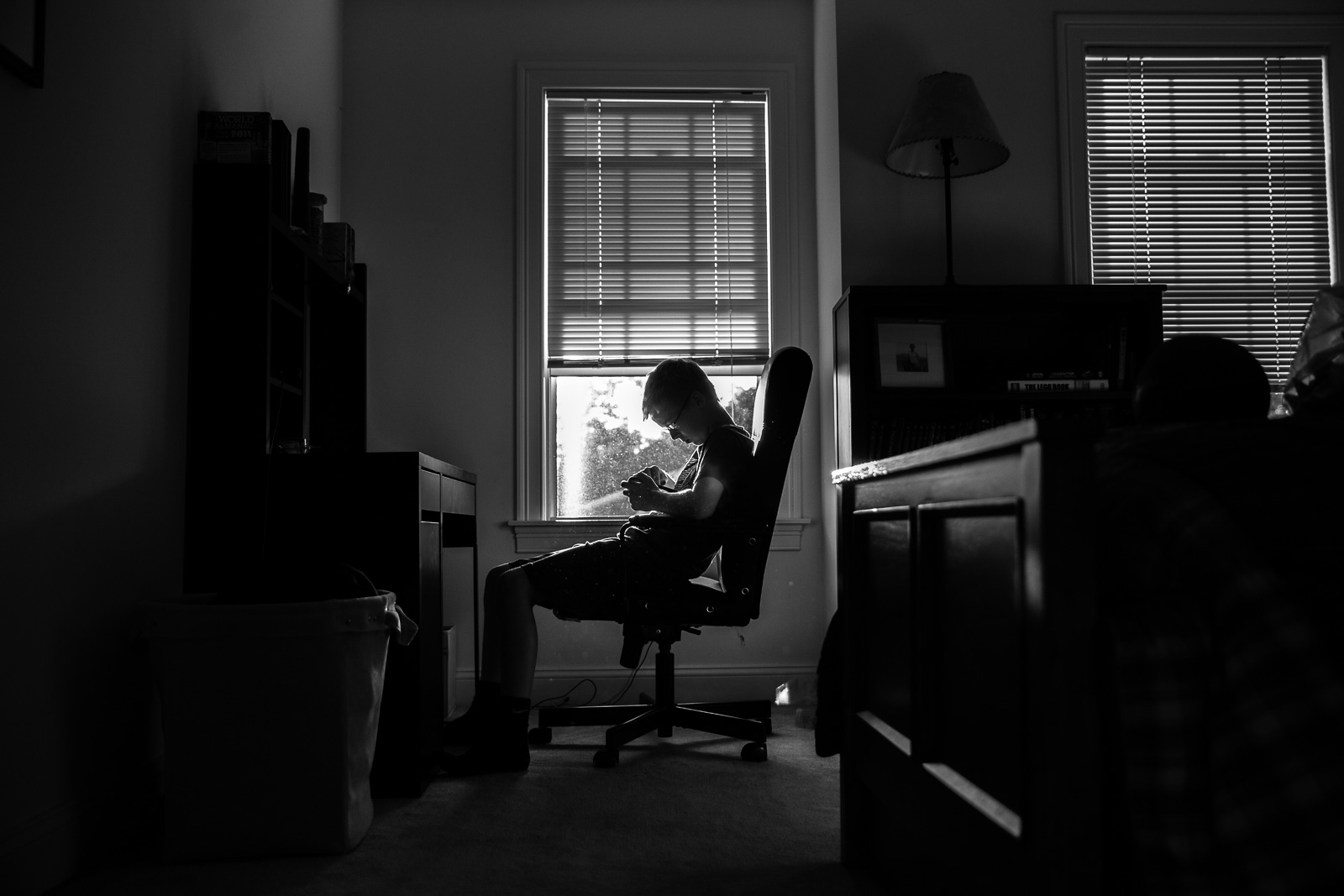 black and white picture of boy sitting in a desk chair by Amy Nowak