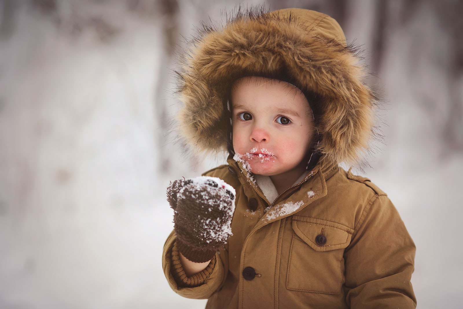 photo of boy eating snow by Amber Walder