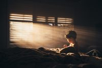 photo of boy sitting on bed with light shining in windows by Amy Shire
