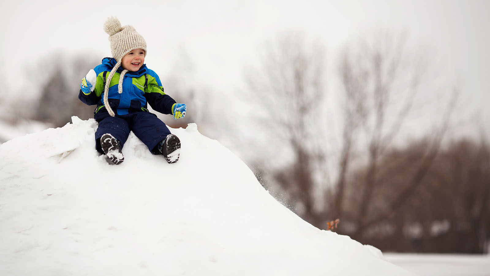 photo of boy smiling and sitting on a pile of snow by Amber Walder