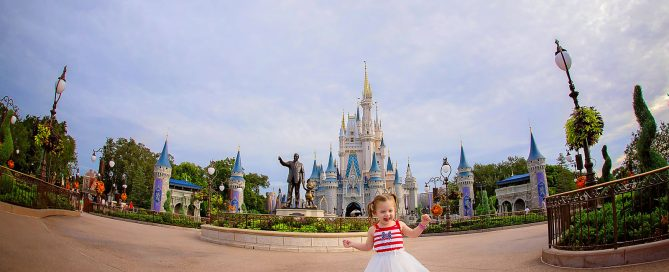 photo of toddler walking in front of Disney World by Dana Nicole Photography