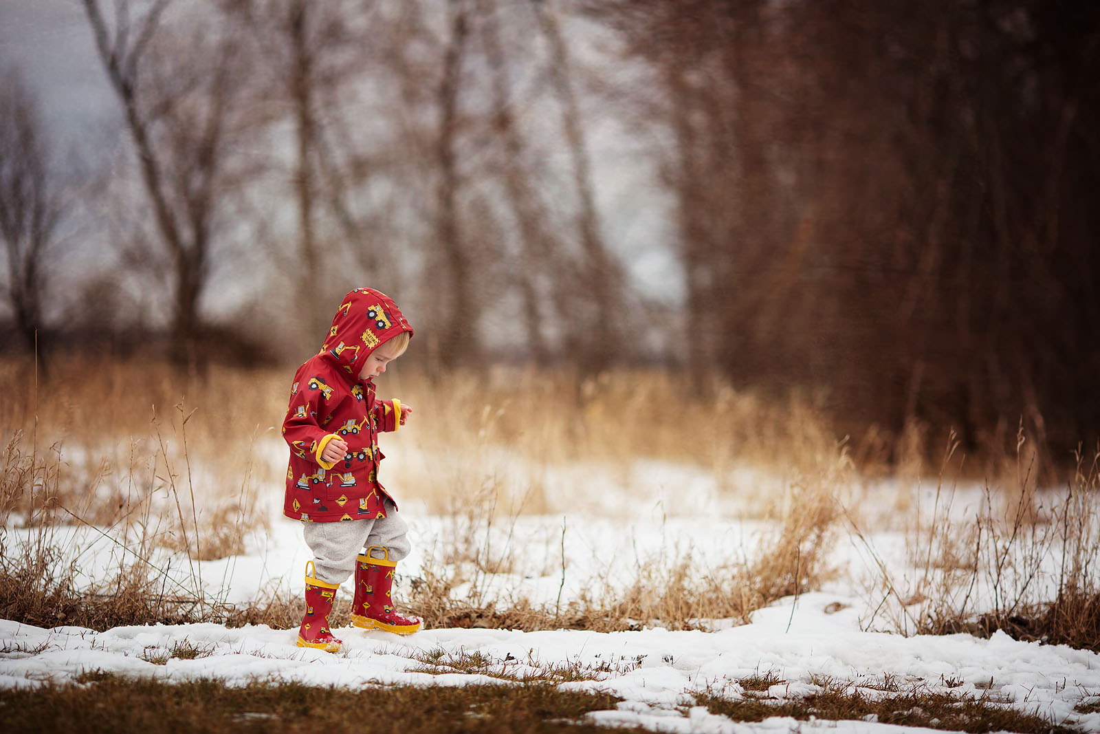 pic of boy in a truck jacket and boots walking in the snow by Amber Walder