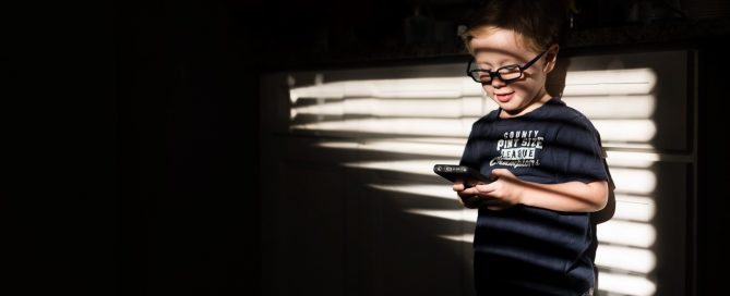 pic of boy playing on an iPhone by Emily Ingalls