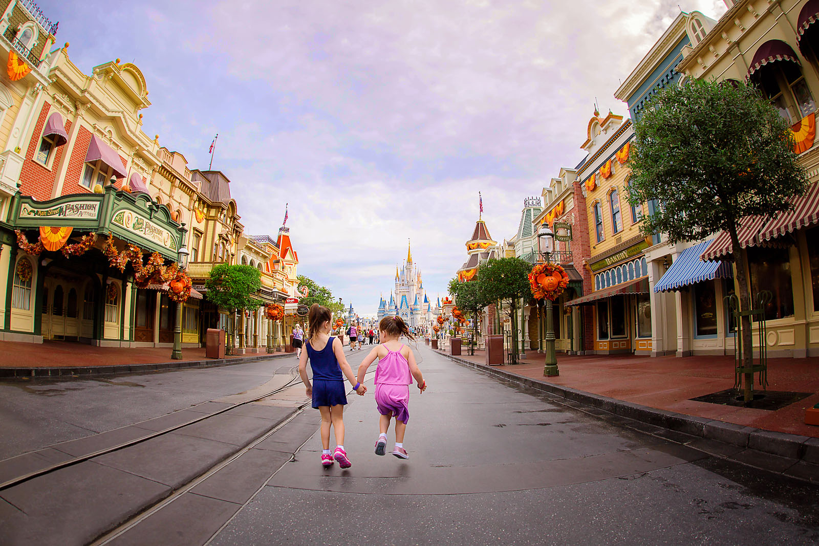 pic of two girls holding hands in front of the Disney World castle by Dana Nicole Photography