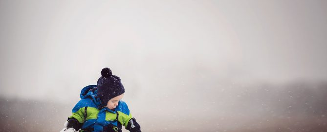 picture of kid playing in the snow by Amber Walder