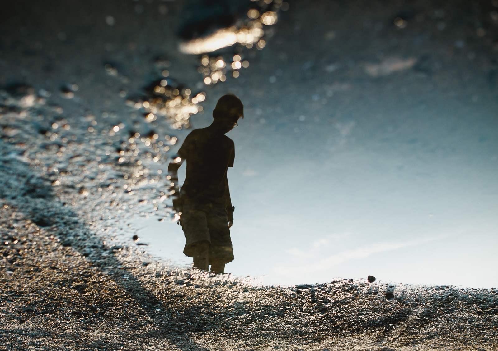 reflection of boy in a water by Amy Nowak