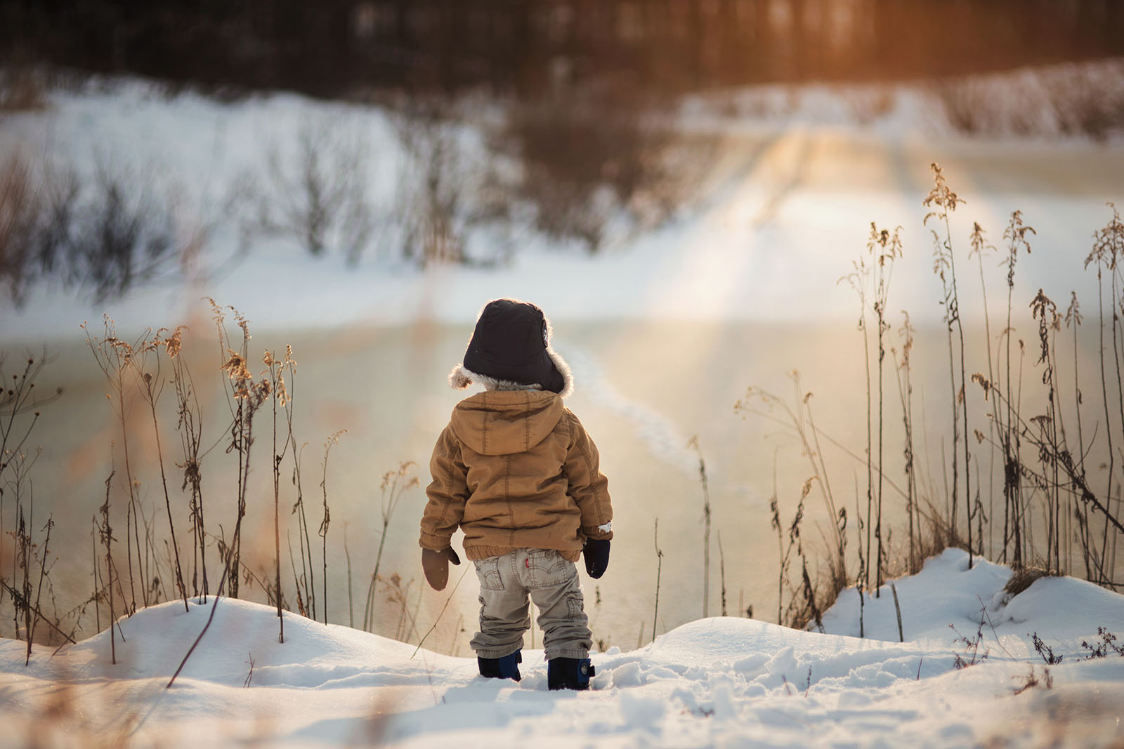 backlit pic of boy by the water covered in snow by Meg Loeks