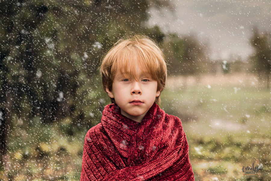 photo of boy in a red blanket with snow falling by Emily Ingalls