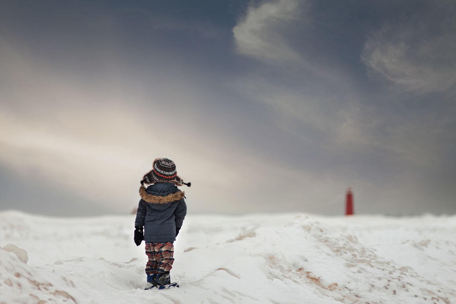 photo of boy walking on the snow by Meg Loeks