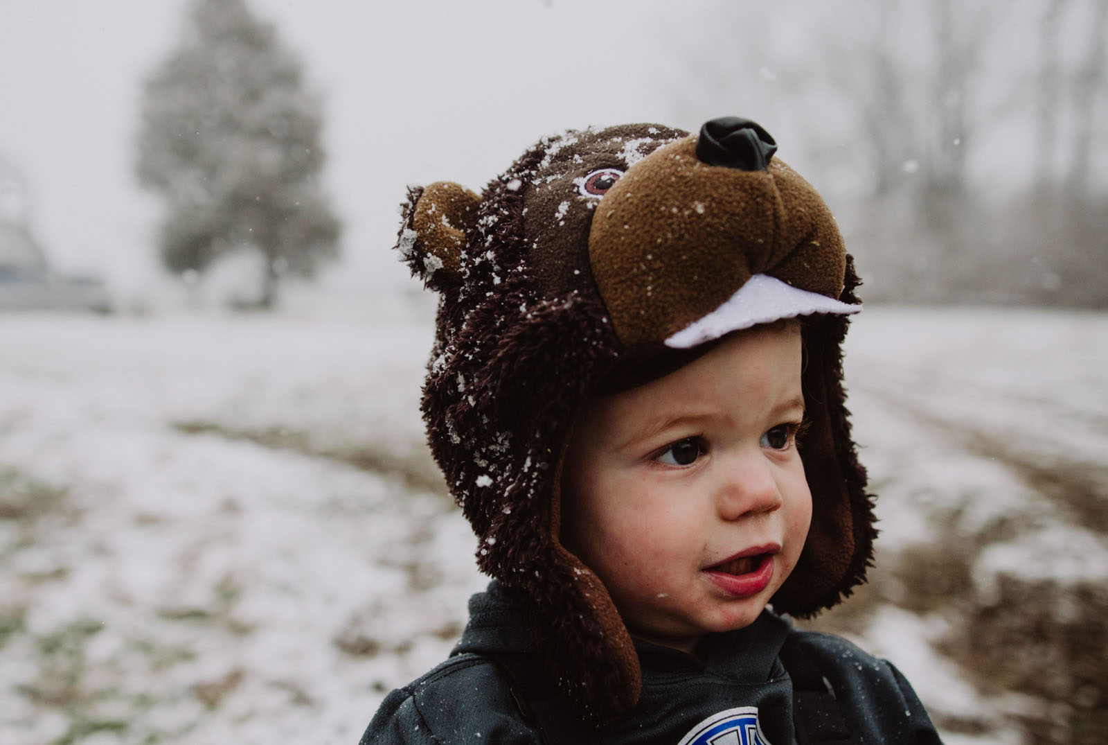 photo of kid standing in the snow by Ashley Manley