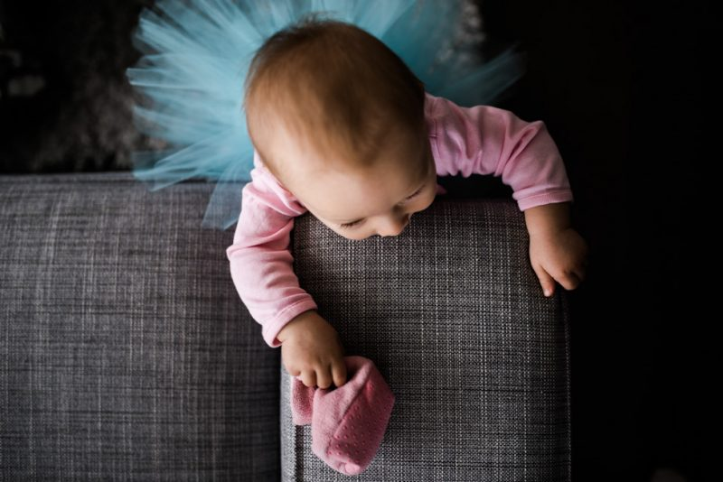 photo of toddler girl standing near the couch with a tutu on by Jenny Diaz