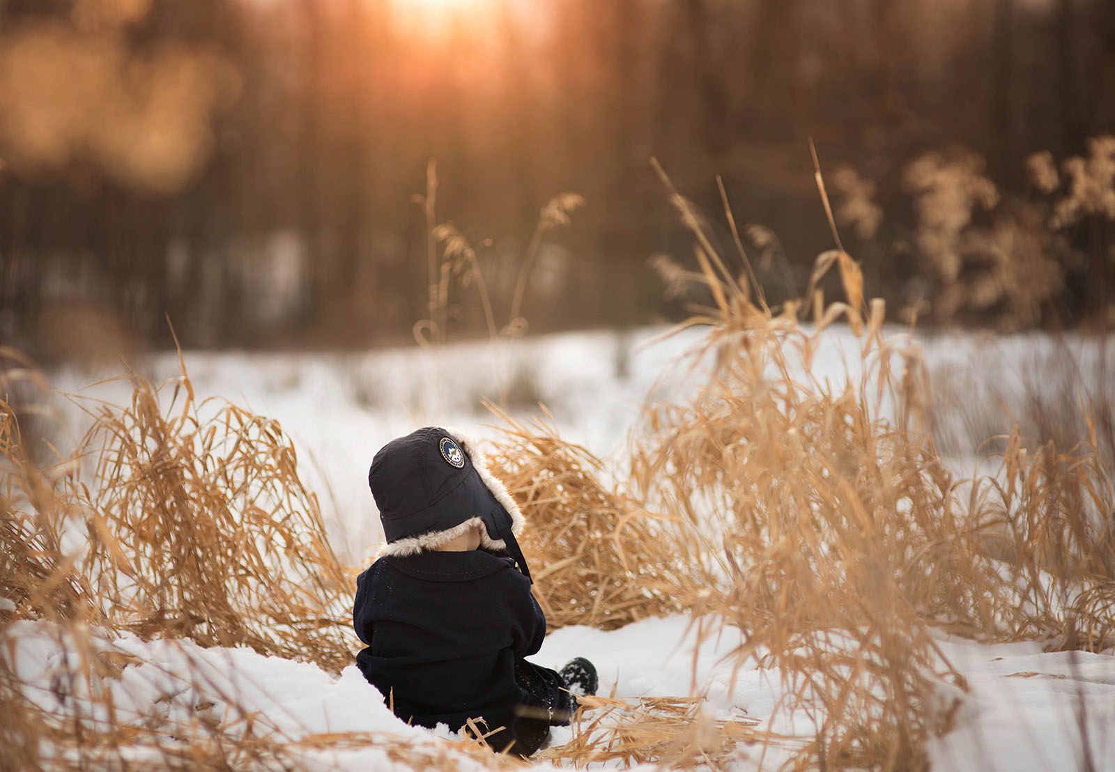 photo of toddler sitting in the snow by Meg Loeks