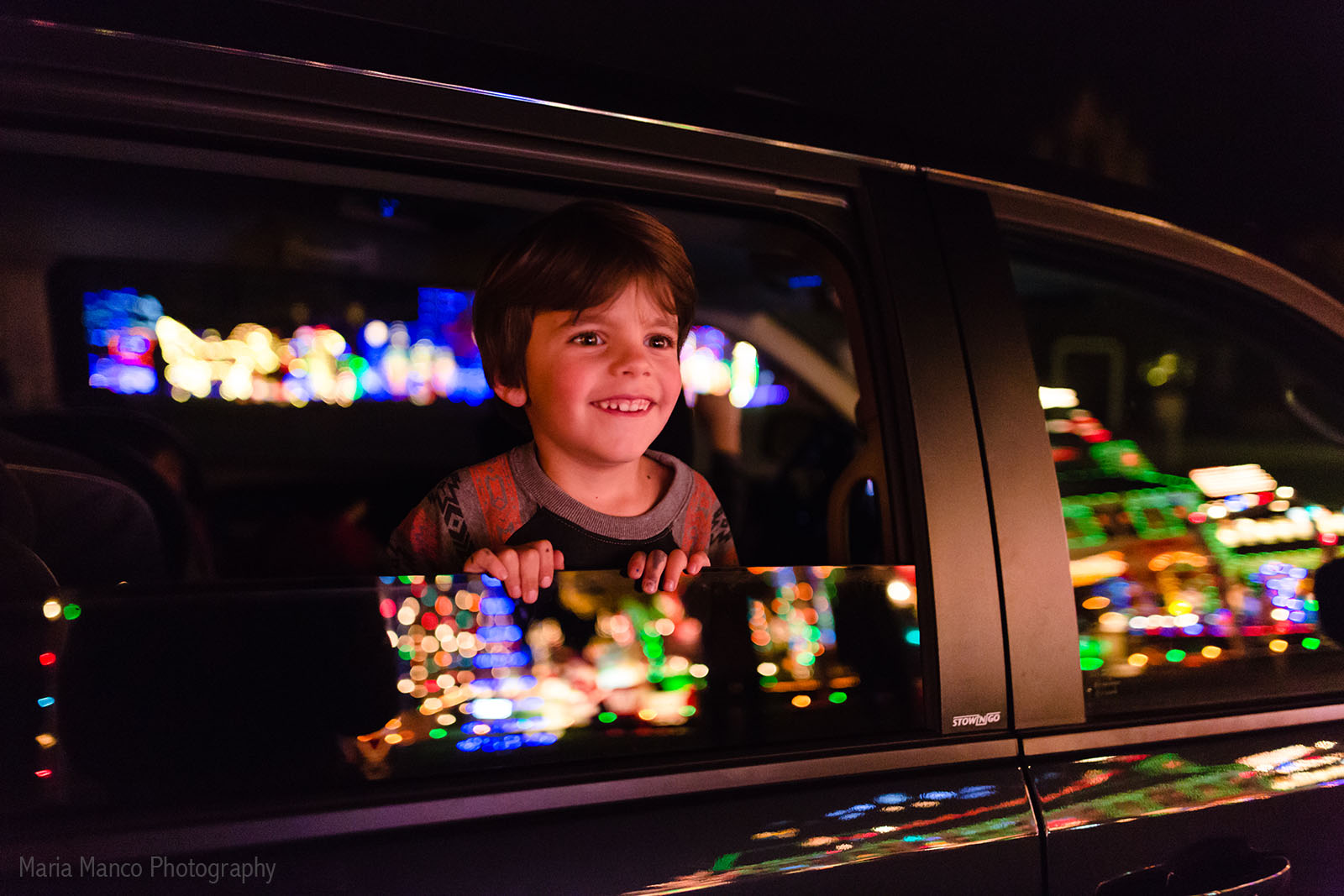 pic of kid looking at Christmas lights outside by Maria Manco