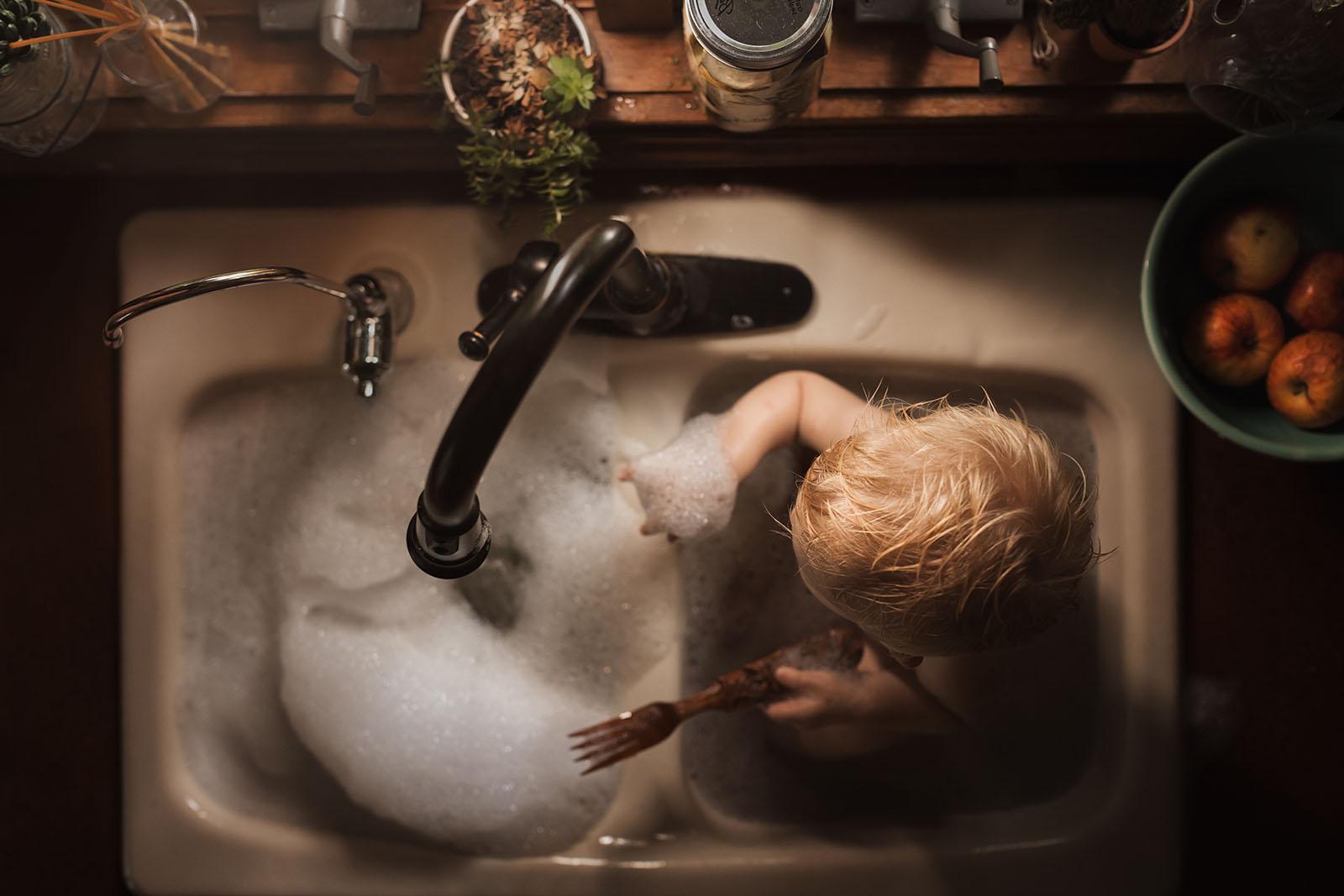 picture of boy taking a sink bath by Meg Loeks