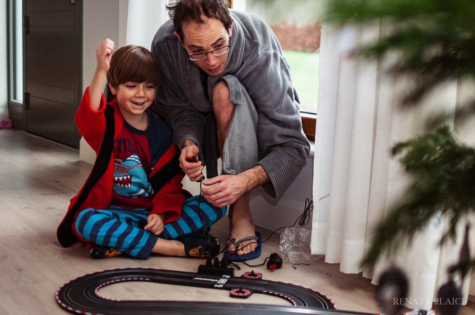 picture of dad and son playing with a race car track by Renata Plaice
