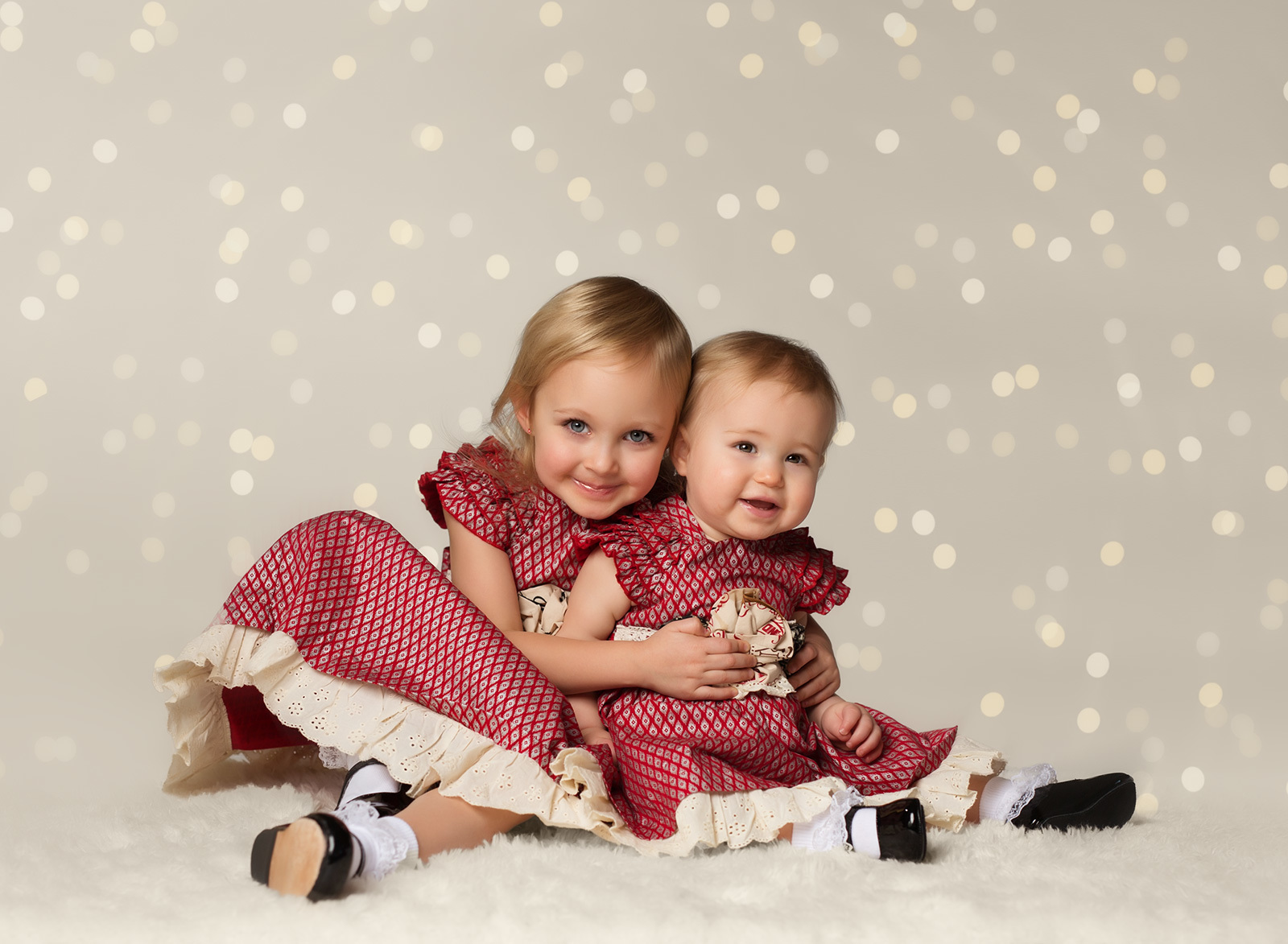 picture of sisters with Christmas lights in the background by Kate Luber