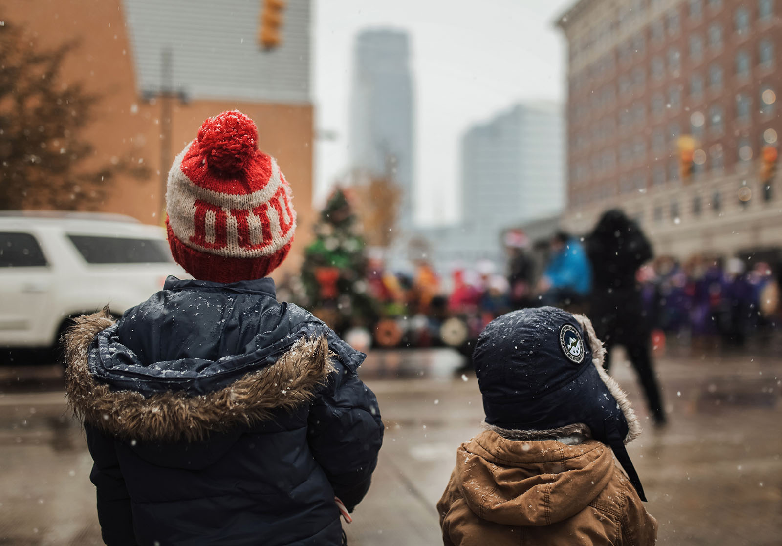 two boys watching a parade in the snow by Meg Loeks