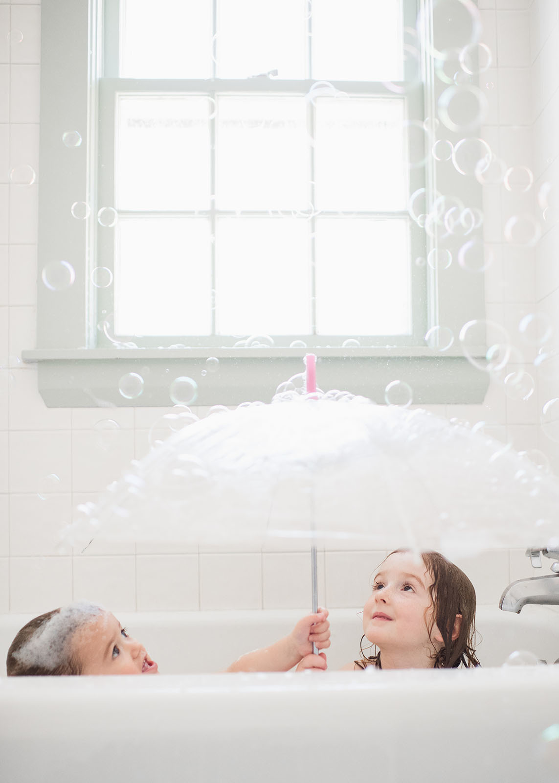 kids playing with an umbrella and bubbles in the bathtub by Liza ...