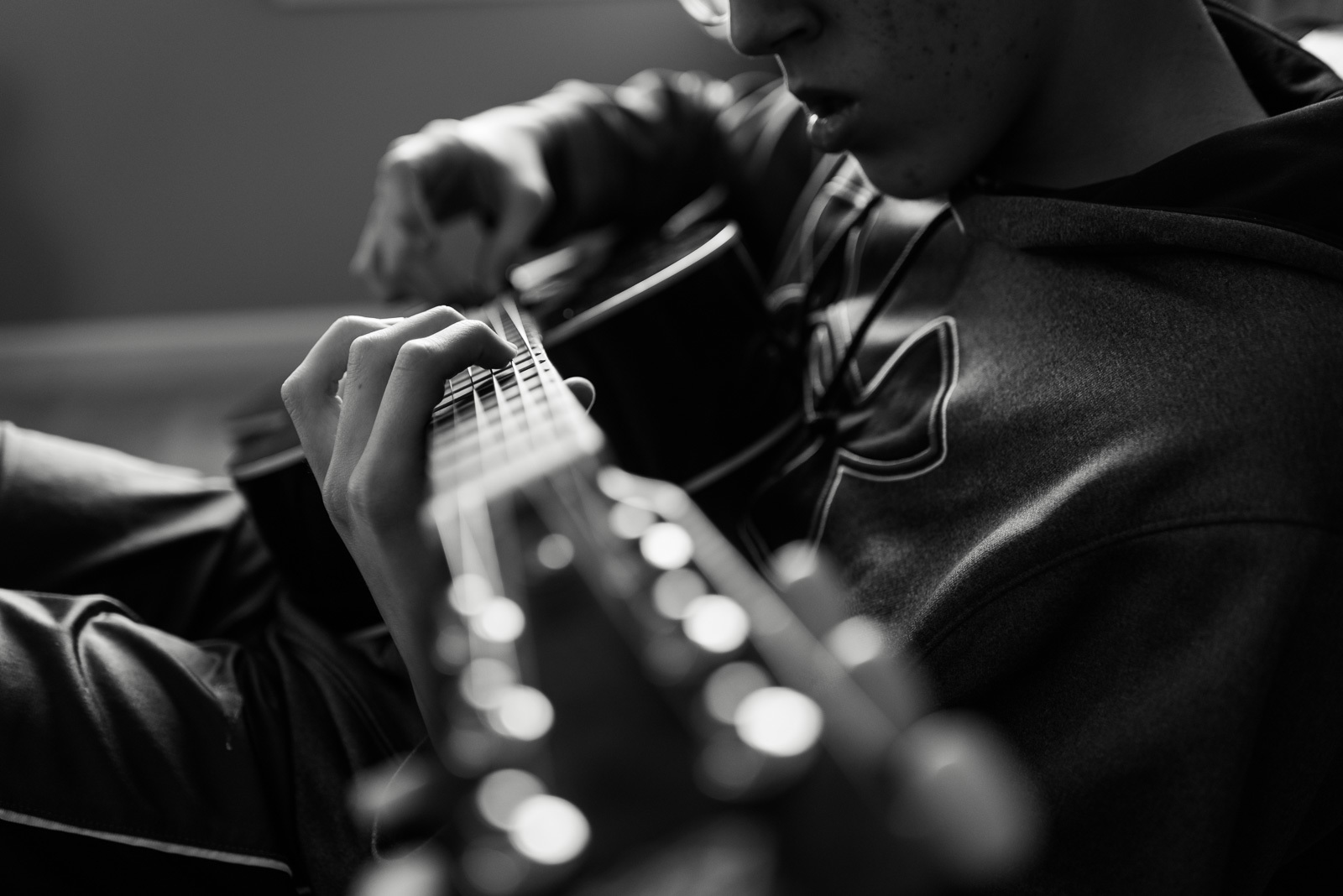 Black and white photo of boy playing a guitar by jonica weiler