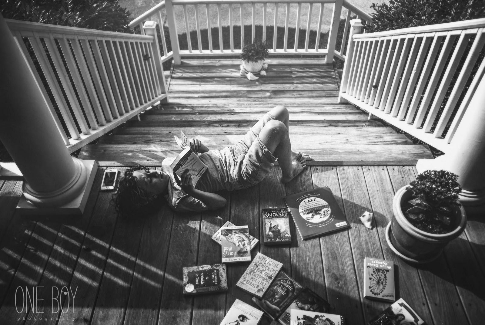 pic of boy reading books on the front porch by Jan Tyler