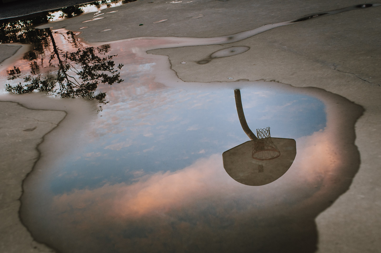 a basketball hoop reflecting in a water puddle by Ebony Logins