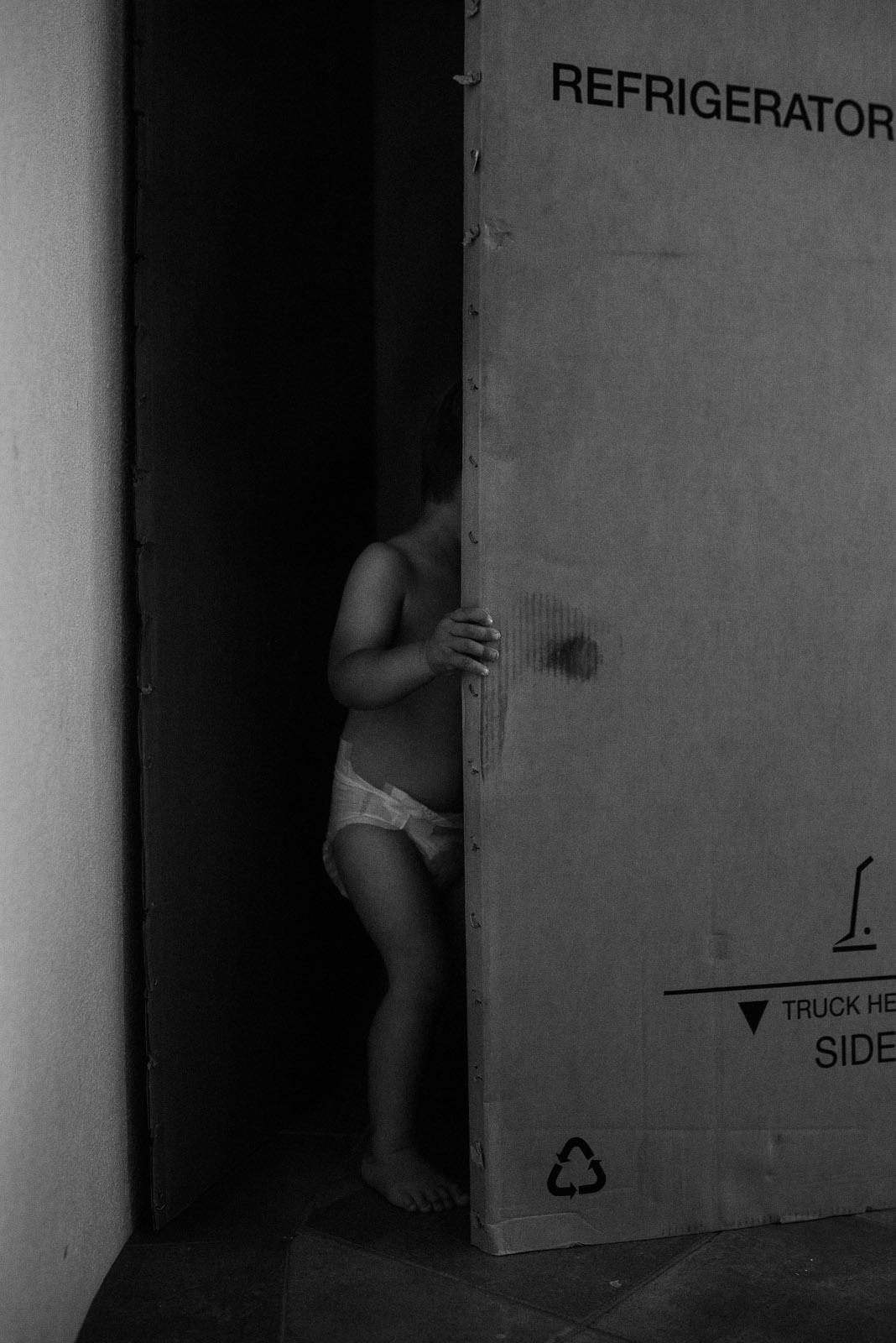 black and white pic of kid behind a door by Elle Walker