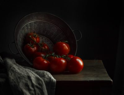 plump red tomatoes on a table by Caroline Jensen