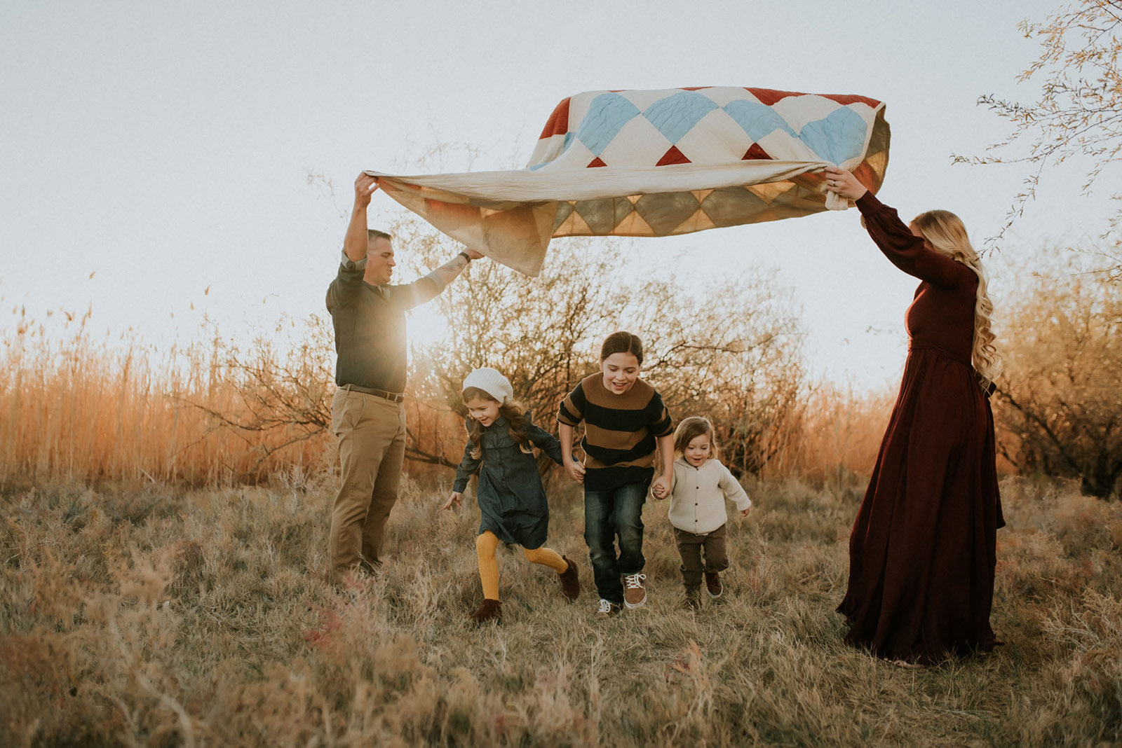 backlit picture of family with a quilt by Jamie Rubeis