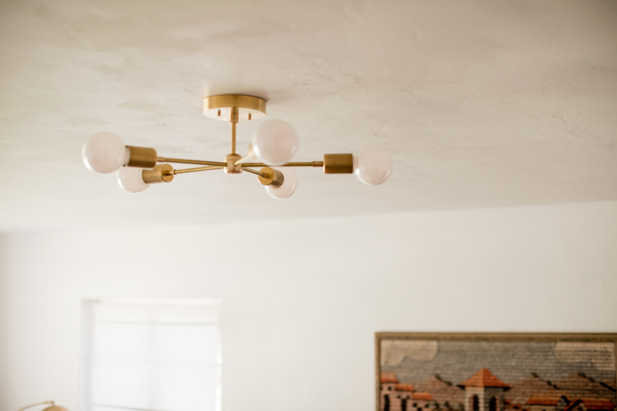 gold ceiling light fixture with white globe lamps